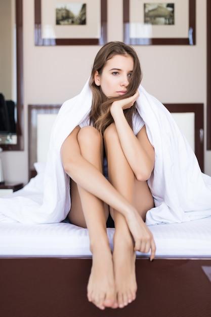 Jeune Femme Pensive Est Assise Avec Une Couverture Sur Sa Tête Au Lit Avec Des Draps Blancs, Concert De L'hôtel, Appartement Moderne Photo gratuit