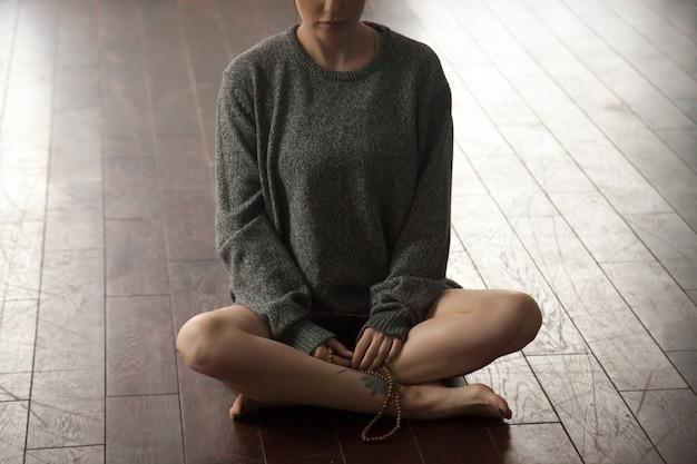 Jeune femme, à, perles, séance, dans, sukhasana, pose Photo gratuit