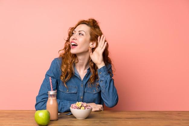 Jeune femme avec petit-déjeuner sur rose isolé Photo Premium