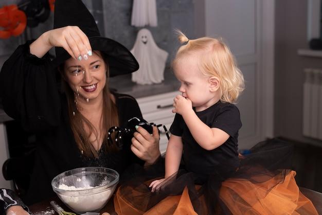 Jeune femme et petit enfant dans la cuisine Photo gratuit