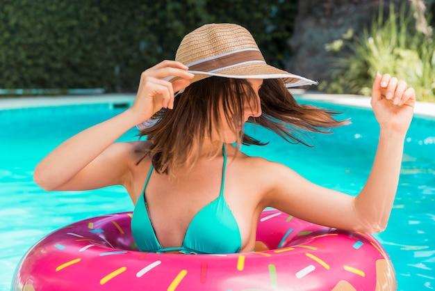 Jeune femme avec piscine cercle en piscine Photo gratuit