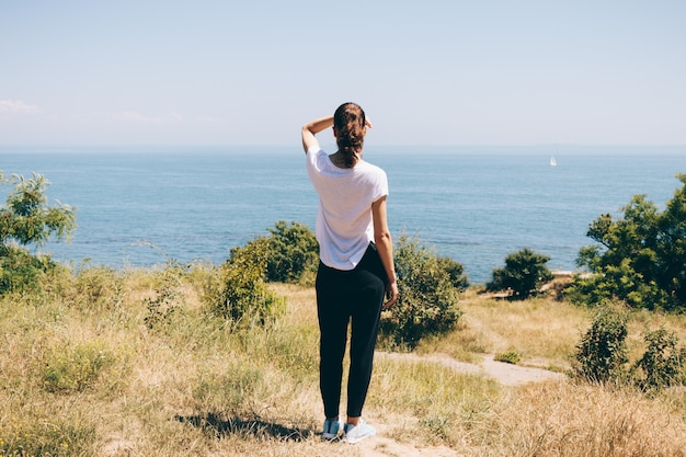 Jeune femme sur la plage en regardant la mer Photo Premium