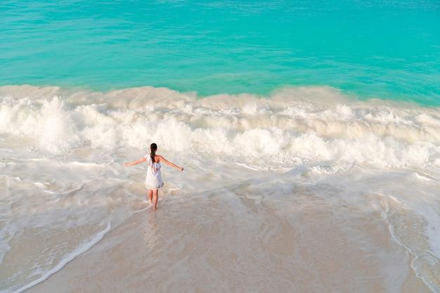 Jeune femme à la plage s'amuser dans les eaux peu profondes. vue de dessus de belle fille au bord de la mer à la lumière de sofft Photo Premium