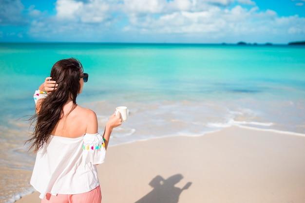 Jeune femme sur la plage vue arrière de la fille avec une tasse de café au bord de la mer Photo Premium