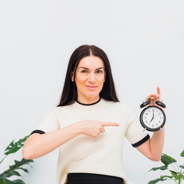 Jeune femme, pointage, horloge Photo gratuit