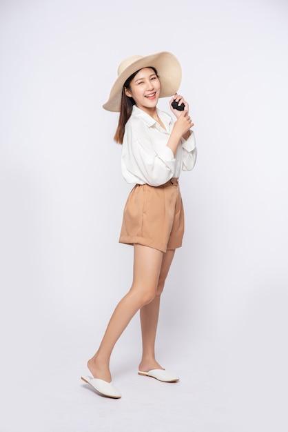 Jeune Femme Portant Une Chemise Blanche Et Un Short, Portant Un Chapeau Et Une Poignée Sur Le Chapeau Photo gratuit