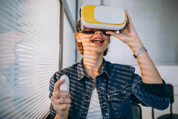 Jeune femme portant des lunettes de réalité virtuelle et jouant à un jeu virtuel en utilisant une télécommande Photo gratuit