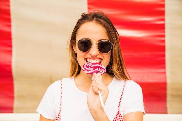 Jeune femme portant des lunettes de soleil mordant sucette Photo gratuit