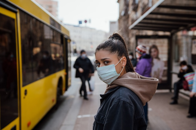 Jeune Femme Portant Un Masque Chirurgical En Plein Air à L'arrêt De Bus Dans La Rue Photo gratuit