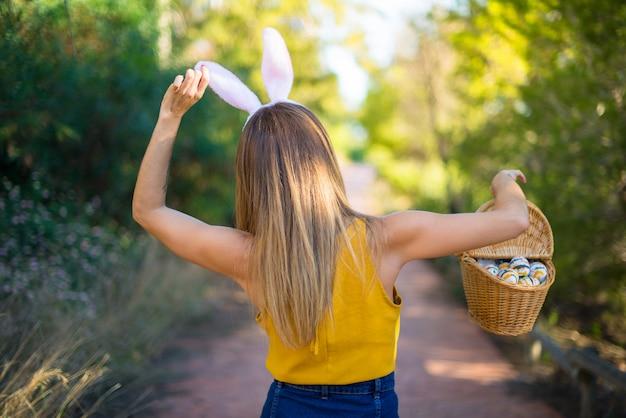 Jeune Femme Portant Des Oreilles De Lapin Et Avec Un Oeuf De Pâques Coloré à L'extérieur Photo Premium