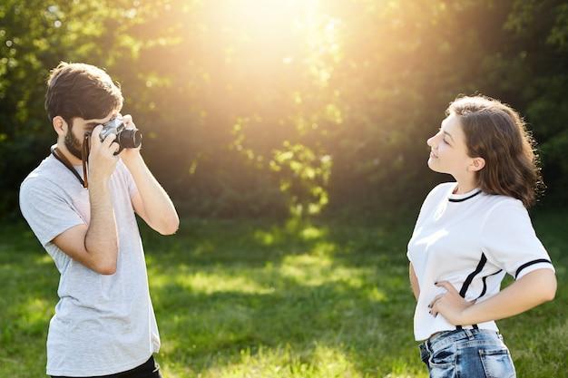 Jeune Femme Portant Un T-shirt Se Présentant à Huis Clos Au Photographe. Jeune Homme Talentueux Avec Appareil Photo Rétro Photographiant Jolie Femme Photo gratuit