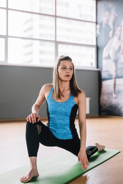 Jeune femme portant des vêtements de sport exerçant dans une salle de sport Photo gratuit
