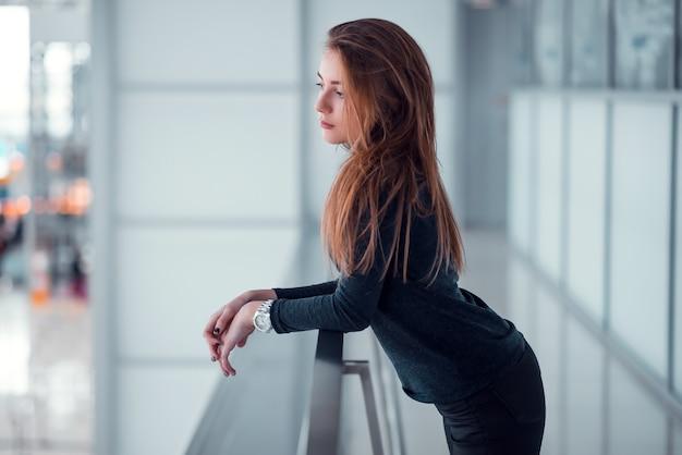 Jeune Femme Posant Sur Un Balcon Vitré. Photo Premium