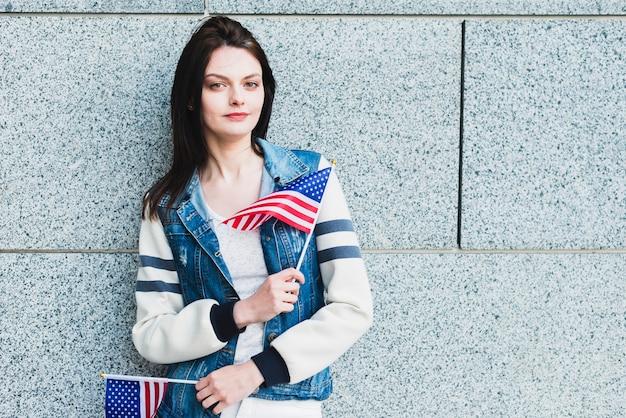 Jeune femme posant avec des drapeaux américains Photo gratuit