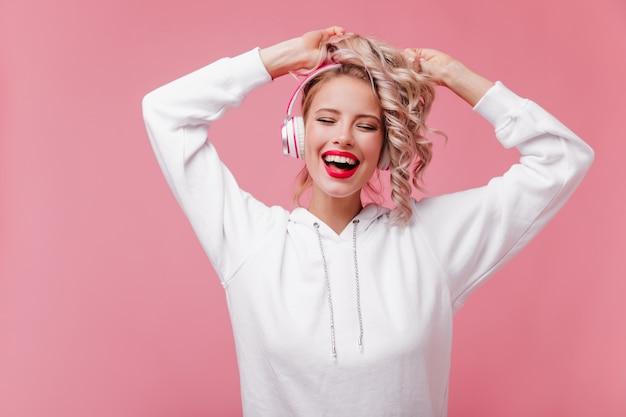 Jeune Femme Posant Et écoutant De La Musique Grâce à Ses écouteurs Roses Photo gratuit