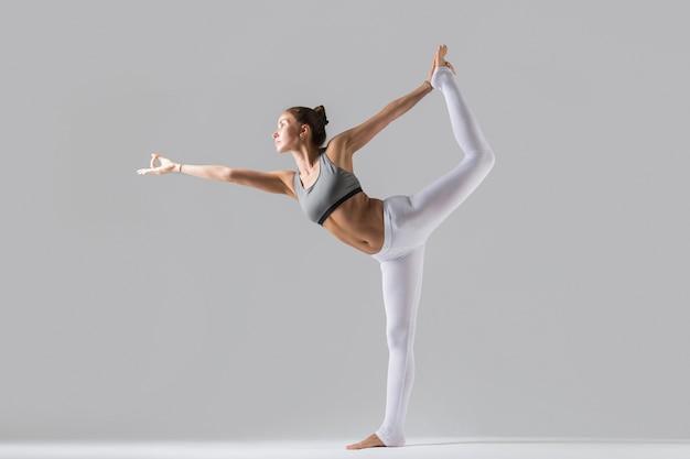 Jeune femme à la pose de natarajasana, fond de studio gris Photo gratuit