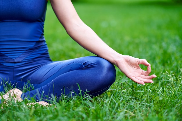 Jeune Femme Pratiquant La Méditation D'yoga Dans La Nature Au Parc. Pose De Lotus. Concept De Mode De Vie Santé Photo Premium