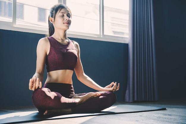 Jeune femme pratiquant le yoga en classe; belle fille ressentant le calme et se détendre en cours de yoga Photo Premium