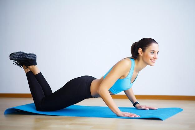 Jeune femme pratiquant le yoga, faisant des exercices dans la nature, l'exercice du flip-the-dog, la pose de camatkarasana, l'exercice, portant des vêtements de sport, pantalon et haut noirs, longueur totale intérieure, mur gris dans un studio de yoga Photo Premium
