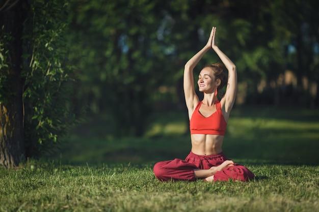 Jeune femme pratiquant le yoga en plein air. femme méditer en plein air dans le parc de la ville d'été. Photo Premium