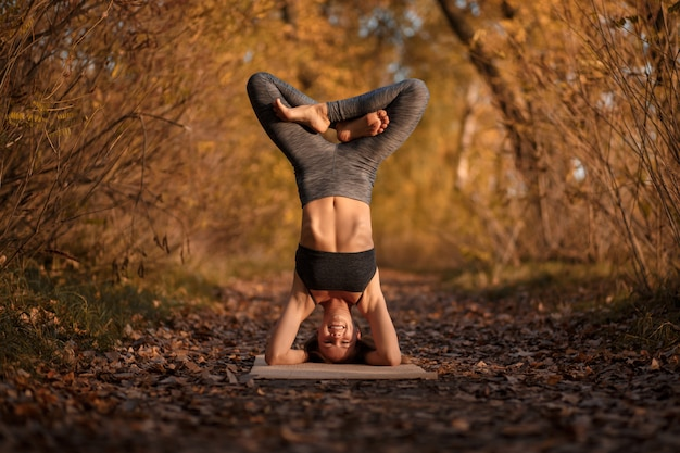 Jeune femme à pratiquer des exercices d'yoga au parc automne avec les feuilles jaunes. mode de vie sportif et récréatif Photo Premium