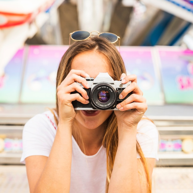 Jeune femme prenant une photo avec l'appareil photo Photo gratuit