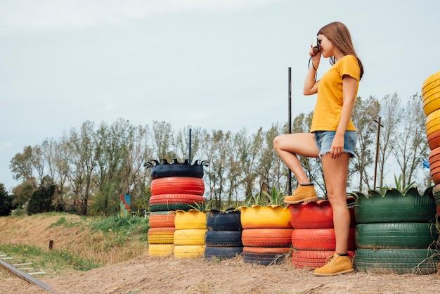 Jeune femme prenant une photo à la campagne Photo gratuit