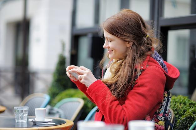 Jeune femme prenant une photo mobile de sa tasse de café dans un café de rue parisien Photo Premium