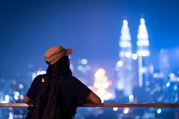 Jeune femme prenant une photo avec son smartphone des tours jumelles petronas à kuala-lumpur le soir Photo Premium