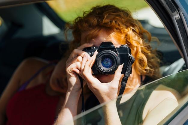 Jeune femme prenant une photo Photo gratuit