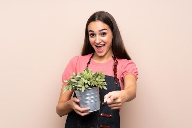 Jeune femme prenant un pot de fleurs et pointant vers l'avant Photo Premium