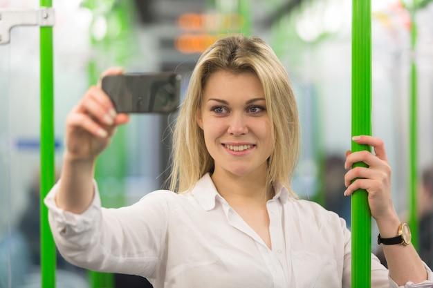 Jeune femme prenant un selfie dans le métro de londres Photo Premium