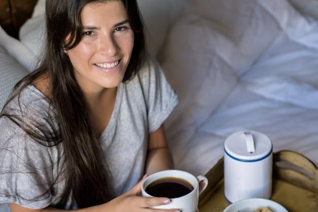 Jeune femme prenant son petit déjeuner au lit Photo Premium