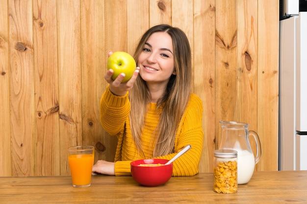 Jeune femme prenant son petit déjeuner dans une cuisine avec une pomme Photo Premium