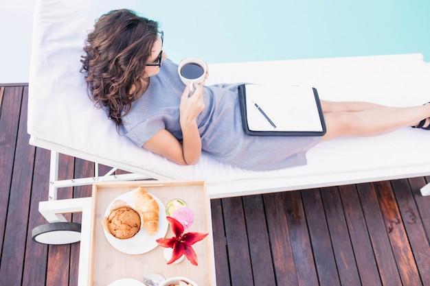 Jeune femme prenant une tasse de thé et se détendre sur une chaise longue au bord de la piscine Photo Premium