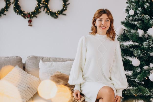 Jeune Femme Près De L'arbre De Noël Photo gratuit