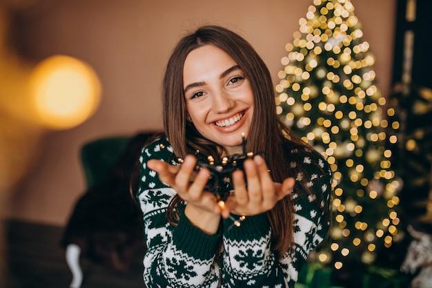 Jeune Femme Près Du Sapin De Noël Avec Des Lumières Rougeoyantes De Noël Photo gratuit
