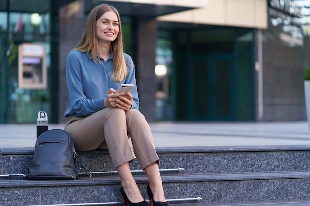Jeune Femme Professionnelle Assise Sur L'escalier En Face Du Bâtiment En Verre, Parler Au Téléphone Mobile Photo gratuit