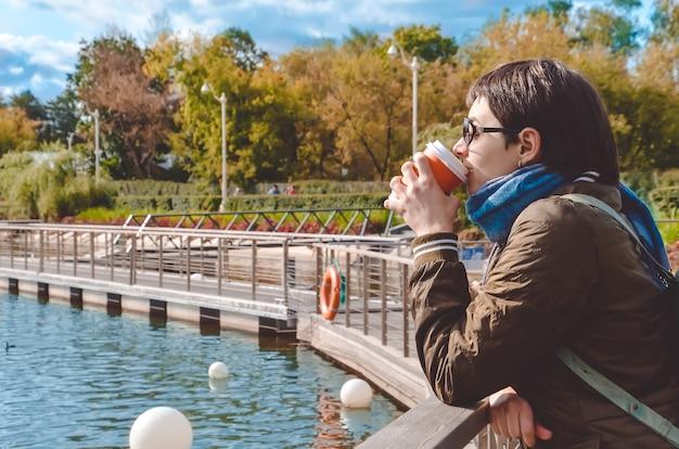 Jeune Femme De Profil De Boire Du Café, Se Dresse Sur La Jetée De L'étang De La Ville Et Regarde L'eau Photo Premium