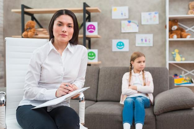 Jeune femme psychologue assise sur une chaise avec le presse-papier et un stylo assis devant une fille dépressive Photo gratuit