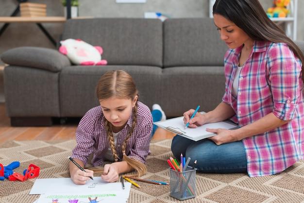 Jeune femme psychologue prenant des notes pendant que la fille dessinait sur du papier blanc Photo gratuit
