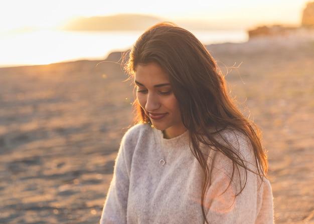 Jeune femme en pull assis sur le bord de mer de sable Photo gratuit