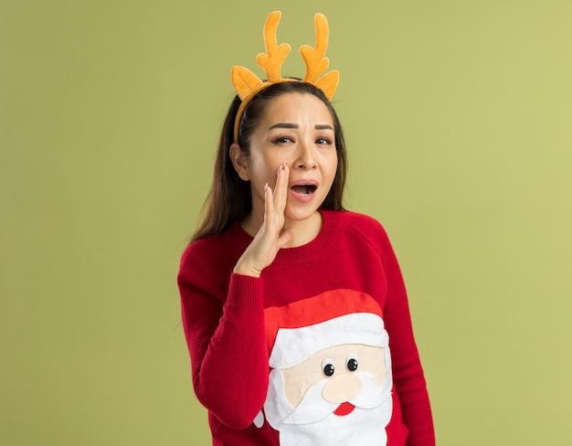 Jeune Femme En Pull De Noël Rouge Portant Une Jante Drôle Avec Des Cornes De Cerf Criant Avec La Main Près De La Bouche Photo gratuit