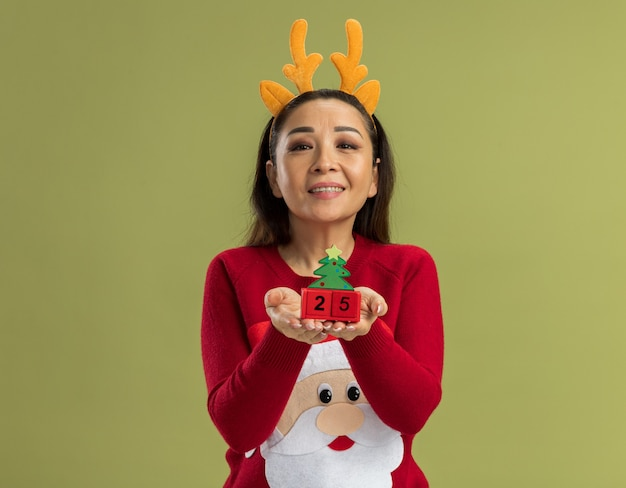 Jeune Femme En Pull De Noël Rouge Portant Une Jante Drôle Avec Des Cornes De Cerf Montrant Des Cubes De Jouet Avec Date Vingt-cinq à La Recherche Avec Happy Face Smiling Photo gratuit
