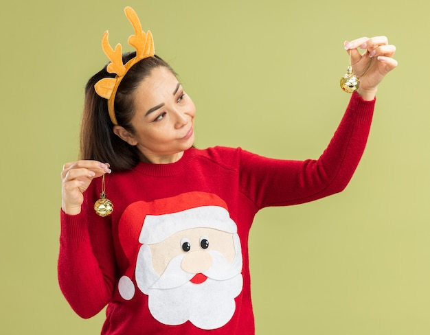 Jeune Femme En Pull De Noël Rouge Portant Une Jante Drôle Avec Des Cornes De Cerf Tenant Des Boules De Noël à La Confusion D'avoir Des Doutes Photo gratuit