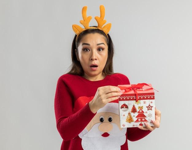 Jeune Femme En Pull De Noël Rouge Portant Une Jante Drôle Avec Des Cornes De Cerf Tenant Un Cadeau De Noël à être Surpris Photo gratuit