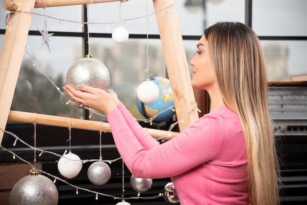 Jeune Femme En Pull Rose Tenant Une Boule De Noël Dorée. Photo De Haute Qualité Photo gratuit