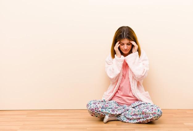 Jeune femme en pyjama assis à la maison, stressée et frustrée, travaillant sous pression, souffrant de maux de tête et troublée de problèmes Photo Premium