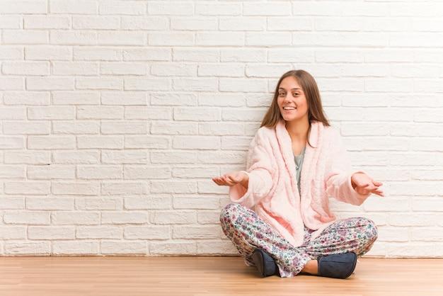 Jeune femme en pyjama invitant à venir Photo Premium