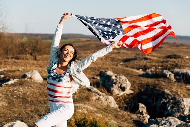 Jeune femme qui court avec des drapeaux américains flottant Photo gratuit